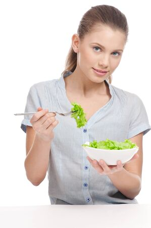 Pretty young woman eating lettuce. Salad. Isolated on the white background photo