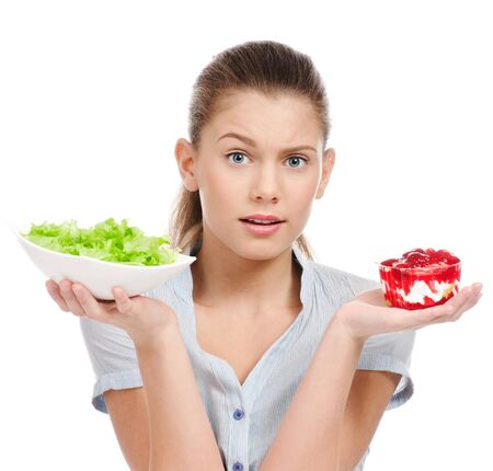 Pretty young woman choice lettuce salad or cake. Isolated on the white background photo