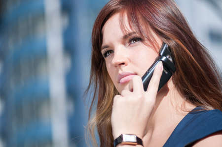Beautiful businesswoman make call by mobile cell phone. Outdoor, over city. photo
