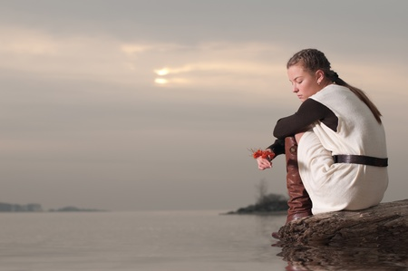Beautiful young lonely woman sitting on sea coast at autumn sunset Stock Photo - 9339081