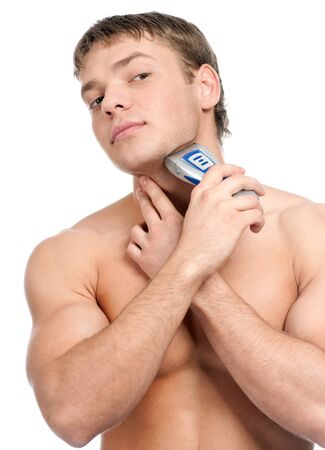 Portrait of a young handsome man shaving as part of his morning routin photo