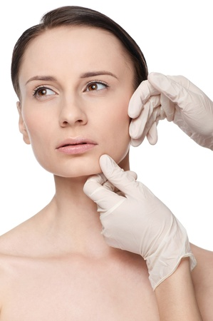 Beautician touch and exam health woman face. Plastic surgery. Isolated Stock Photo - 9394921