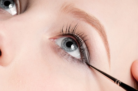 Beautiful young adult woman applying cosmetic paint brush - close-up portrait of eye shadow zone photo