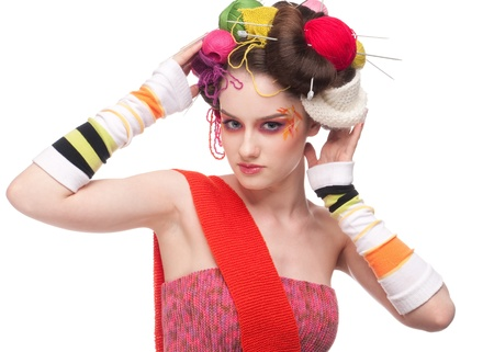 Closeup portrait of beautiful fashion woman with color face art. All in knitting style. Wool balls. photo