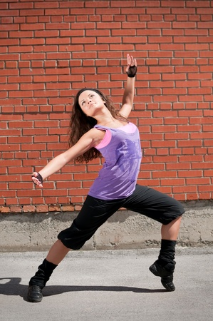 Beautiful teenage girl dancing hip-hop over red brick wall photo