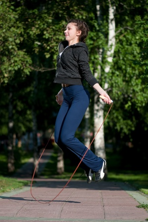 Beautiful young woman doing  exercise with skipping rope at park. Jumping photo
