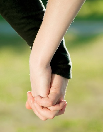 Concept shoot of friendship and love of man and woman: two hands over sun ray and nature Stock Photo - 9452687
