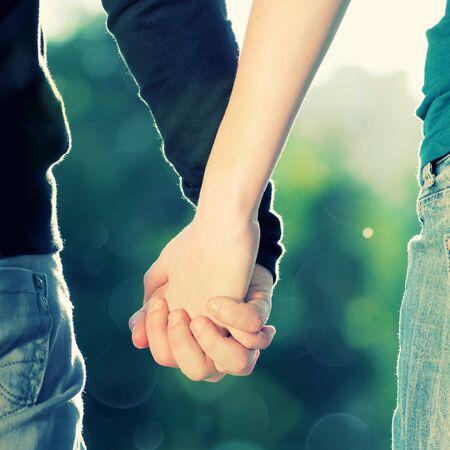 Brote de concepto de la amistad y el amor de hombre y mujer: dos manos sobre los rayos de sol y de la naturaleza Foto de archivo - 9452667