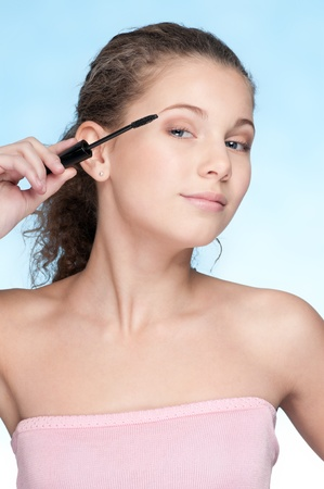 Closeup portrait of young beautiful girl with perfect skin and curly hair. Mascara make up by brush photo