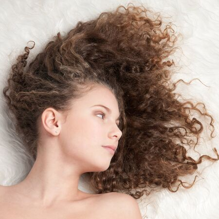 Closeup portrait of young emotional beautiful girl with perfect curly hair. Lying on white fur bed photo