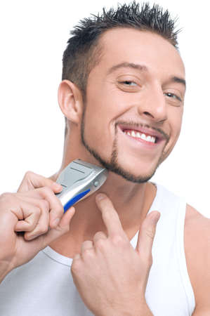 Close up portrait of young handsome man with perfect skin and hair. Shaving by electric shaver photo