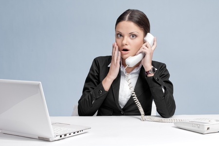 Casual scared  business woman in office working with white table, laptop and talking by phone. Surprise! Stock Photo - 9452744