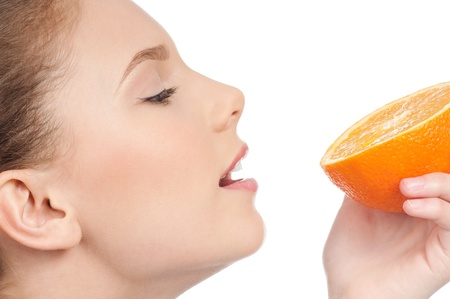 Pretty young woman with half orange isolated on the white background photo