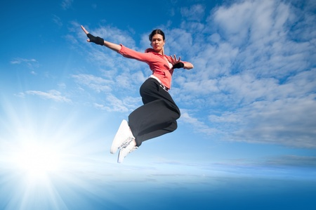urban style: Beautiful sport woman in urban sportswear jumping and fly over blue sky with clouds and sun beam Stock Photo