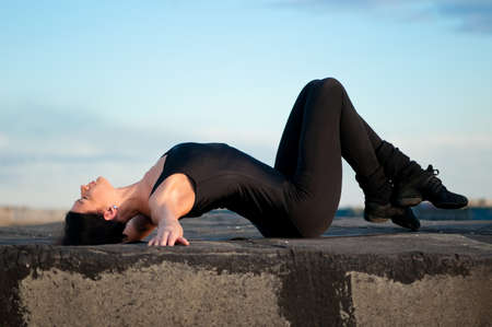 dancing woman in modern pilates style over urban city landscape and blue sky. Yoga photo