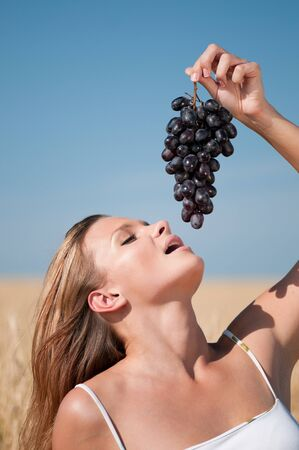 Beautiful woman with perfect hair and skin posing in wheat field and eating grapes. Summer picnic. photo