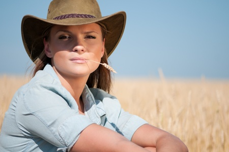 Beautiful cowboy woman with perfect hair and skin posing in country wheat field Stock Photo - 9566581