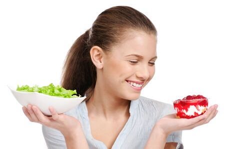 Pretty young woman choice lettuce salad or cake. Isolated on the white background Stock Photo