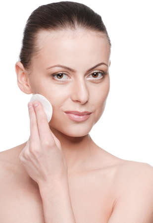Closeup portrait of young beautiful woman with perfect skin. Applying clean sponge. Isolated photo
