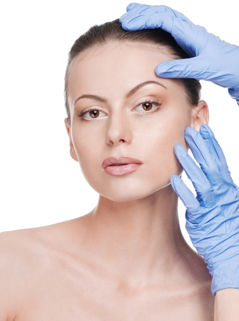 Beautician touch and exam health woman face. Plastic surgery. Isolated Stock Photo - 9566347