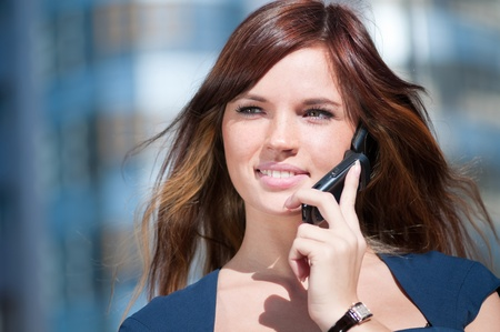 Young business woman using mobile cell phone over city background. Student Stock Photo