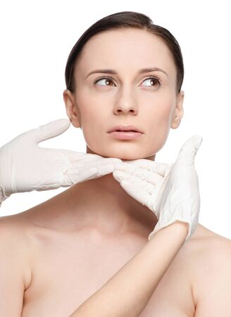 Beautician touch and exam health woman face. Plastic surgery. Isolated Stock Photo - 9633043