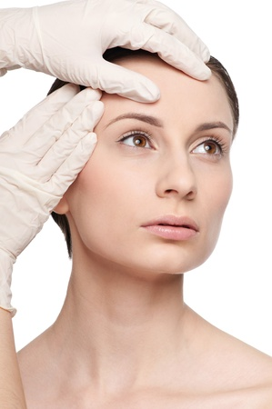 Beautician touch and exam health woman face. Plastic surgery. Isolated Stock Photo - 9633076