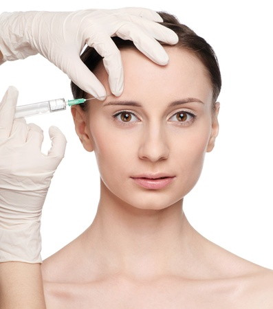 Cosmetic botox injection in the female face. Eyebrow zone. Isolated Stock Photo - 9633014