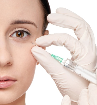 Cosmetic botox injection in the female face. Eye zone. Isolated Stock Photo - 9632995