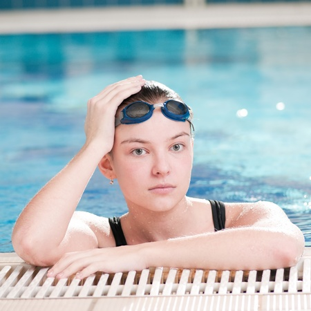 Portrait of a young woman in goggles in swimming pool Stock Photo - 9632729