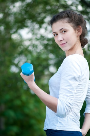 Beautiful young woman doing  exercise with dumbbell on green grass at park. photo