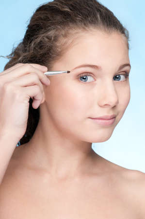 Closeup portrait of young beautiful girl with perfect skin and curly hair. Eye zone shadow make up by thin  brush photo