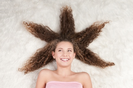 Closeup portrait of young emotional playful girl with perfect curly hair. Lying on white fur bed photo