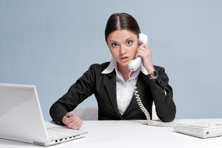 Casual angry business woman in office working with white table, laptop and talking by phone. Strict! photo