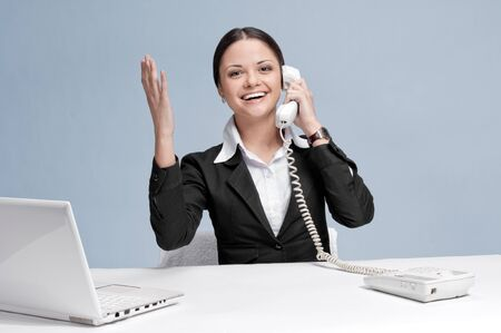 Casual business woman in office working with white table, laptop and talking by phone. Success! photo