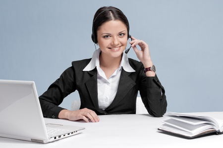 Busy business woman in office place communicate by wireless headset over white table, laptop and diary. photo