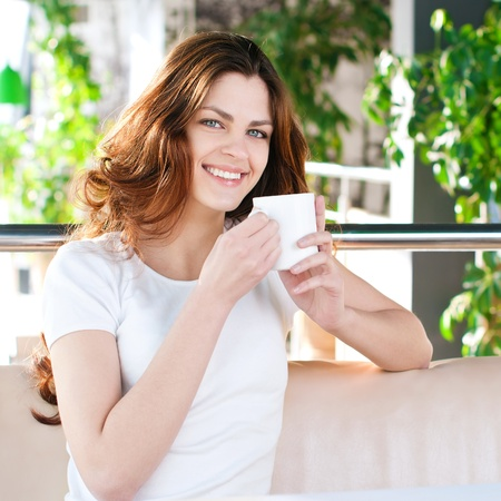 A young attractive woman sitting in a cafe with a coffe photo