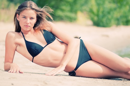 Beautiful young woman ralaxing on sand beach at summer day photo