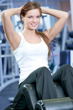 Beautiful sport woman doing press fitness exercise at sport gym photo
