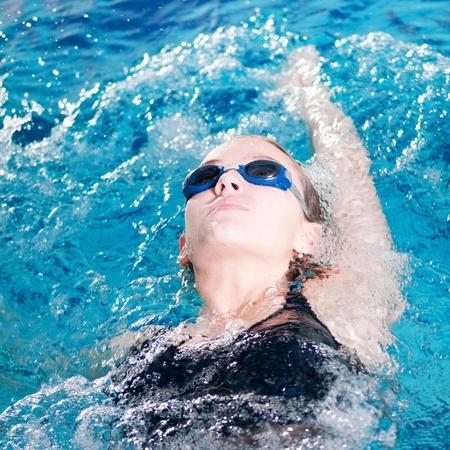 teenage girl swimming in swim meet doing backstroke photo