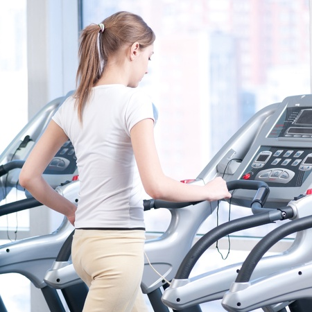 Young woman at the gym exercising. Run on on a machine. Stock Photo - 9805882