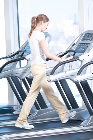 Young woman at the gym exercising. Run on on a machine. Stock Photo - 9805908