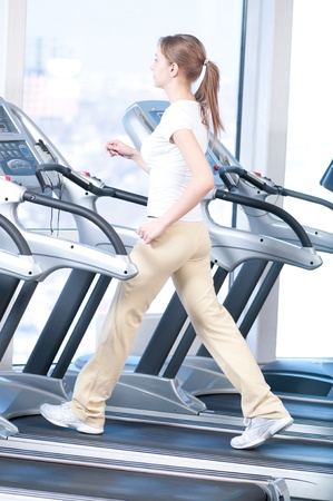 Young woman at the gym exercising. Run on on a machine. Stock Photo - 9805938