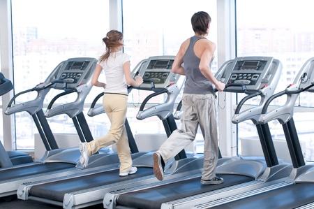 uomo palestra: Giovane donna e uomo presso la palestra di esercizio. Eseguire su una macchina. Archivio Fotografico