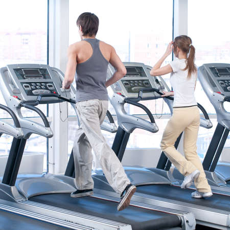Young woman and man at the gym exercising. Run on on a machine. Stock Photo - 9805910