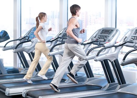 Young woman and man at the gym exercising. Run on on a machine. photo