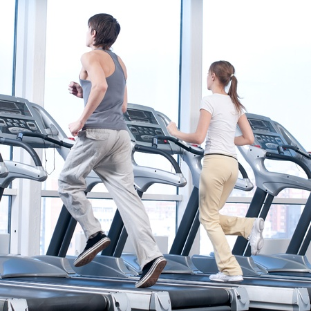 Young woman and man at the gym exercising. Run on on a machine. Stock Photo - 9805887