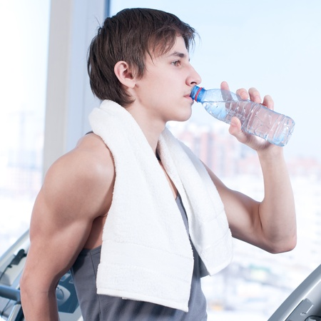 Portrait of a man at the gym drinking water photo