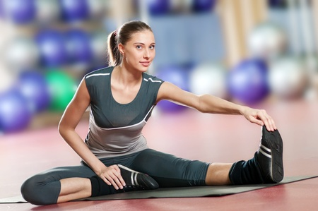 Beautiful sport woman doing stretching fitness exercise at sport gym. Yoga Stock Photo - 9805937