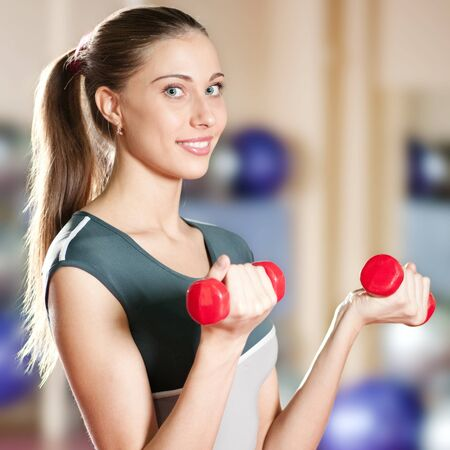 Beautiful sport woman doing power fitness exercise at sport gym. Dumbbell Stock Photo - 9805888